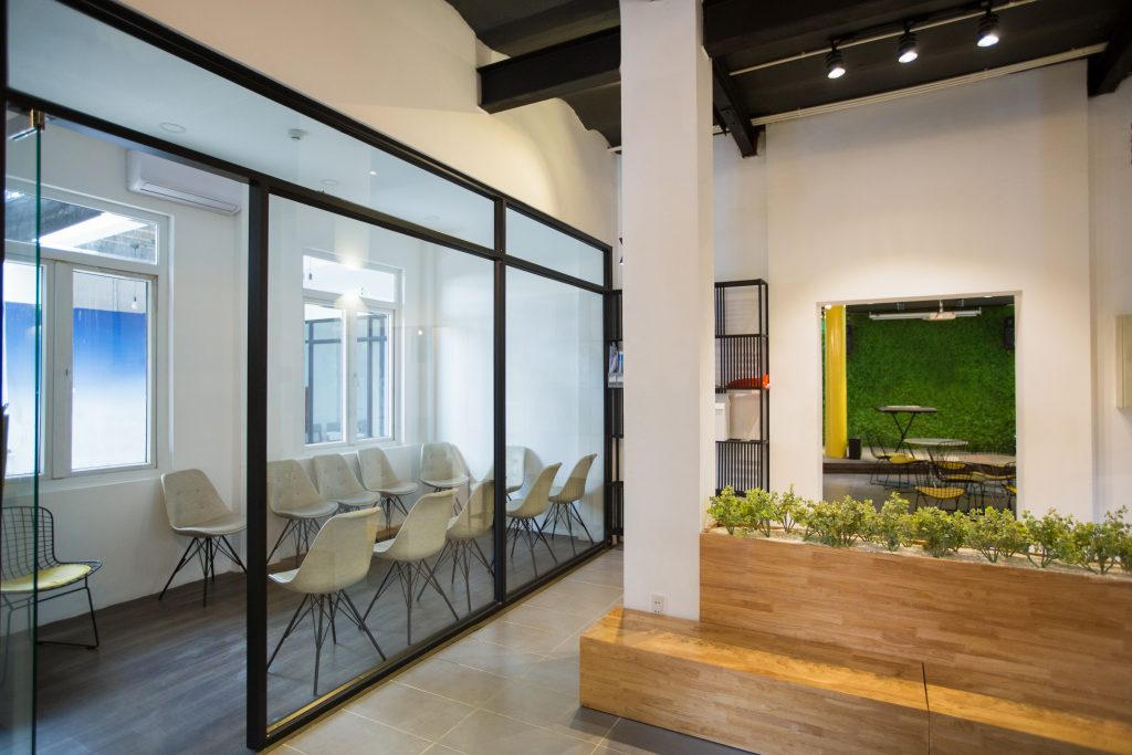 Nobody in office lobby with wooden bench. White wall with column and shelves. Green plants as part of interior. Many chairs behind glassy wall. Business center concept
